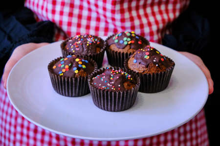 A woman in a plaid apron holding a plate. In the hands of the girl's chocolate muffins. Pinafore in red cell. Homemade cakes in women's hands. Stock Photo
