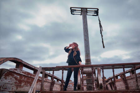 A woman sailor on a pirate ship looks into the distance in search of land