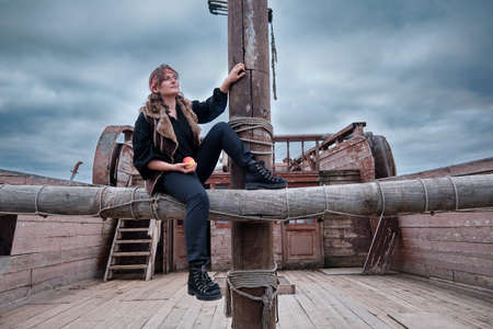 A rogue woman sits near the mast of an old pirate ship Standard-Bild
