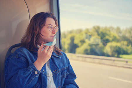 Woman takes off medical mask in public transport. A female tourist took off her face mask on a bus