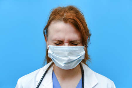 Portrait of a doctor woman with sad facial expression, close up. Nurse in a blue uniform and a medical mask on a blue background.
