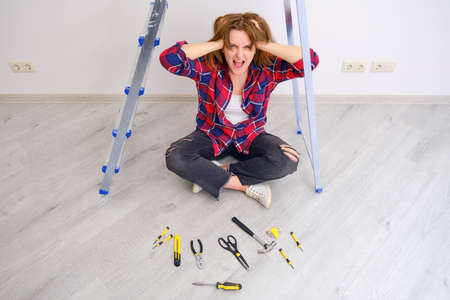 A woman screams because of the difficulty of carrying out repairs on her own. Laid out construction tools on the floor