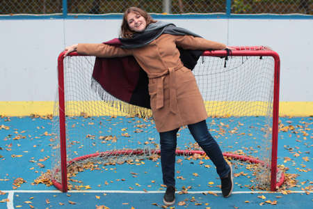 Outdoor play area on the street. A young woman stands at the gate of the hockey field. Autumn weather on the open sports field with blue coating.
