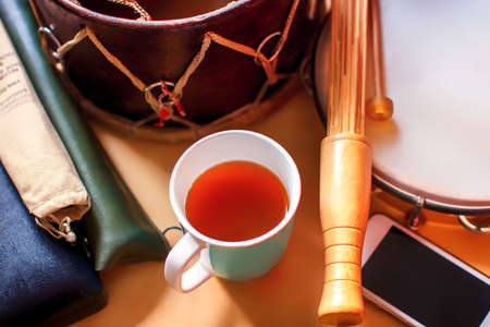 Composition of ethnic musical instruments, telephone and a Cup of tea. Drum, cases with flutes and tambourine on the table. Modern and retro together