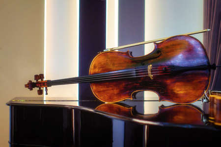 The violin lies on the piano and is reflected in the polished wood. Stringed musical instrument on the piano in the concert hall, before rehearsal Archivio Fotografico