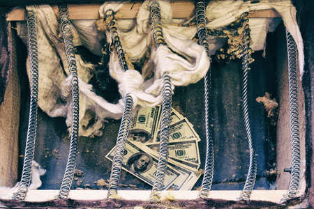 Money is hidden in an old spring sofa. Stash of us dollars in ancient furniture at home