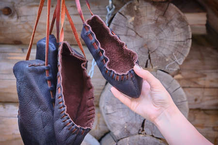Woman holding a retro Shoe made of rough leather. The shoes are vintage style from primitive material. Banco de Imagens