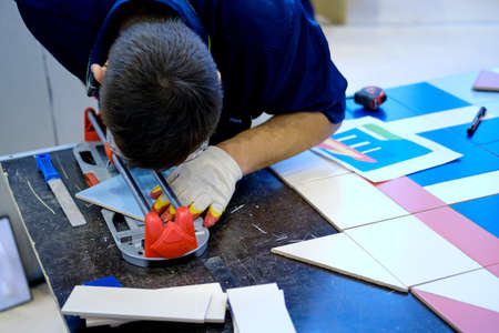 A man cuts ceramic material with a tile cutter, close-up