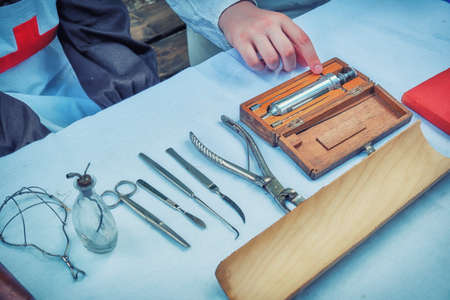 Ancient hospital for treatment soldiers on battlefield - 18th or 19th century. Forceps, syringe, scissors, scalpel and other medical instruments on the table. Medicine in a field military hospital.