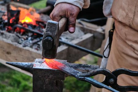 Hammer blow on hot workpiece is in the grip of blacksmith. Brazier, red-hot billet and blacksmith's hand with a sledgehammer. The process of forging iron in the open air.