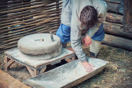 The man is engaged in flour milling on a manual mill. Rural life for the production of flour by grinding wheat.