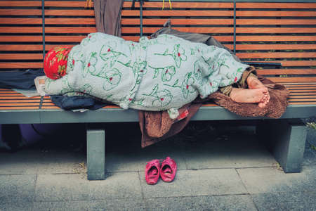 Grandma homeless in clean tidy clothes sleeping on a bench. Granny Stray in the city off his shoes and lay down on your belongings. In the city Park sleeping old lady homeless. Foto de archivo