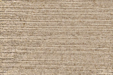 Texture of an old worn carpet, background with a beige pattern