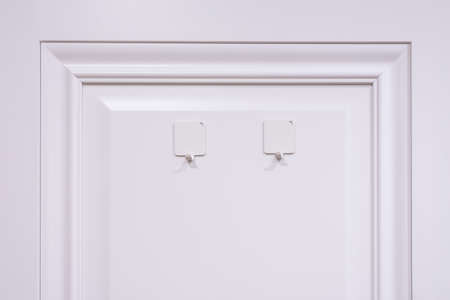 White clothes hooks on the door, close-up