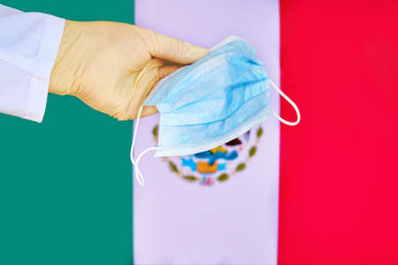 Protective mask in Mexico, concept coronavirus pandemic. Hand in a medical glove holds a mask to protect from the pandemic flu virus among Mexican.