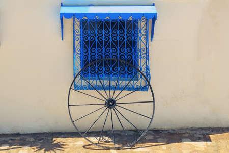 White wall, blue window with lattice ornament and wheel in Sidi Bou Said, Tunisia
