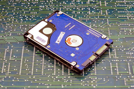 Hard disk on the background of the circuit board Imagens