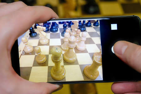 Hand with phone against chess piece