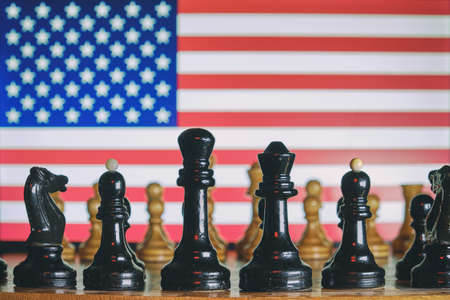 US flag on the background of a chessboard with pieces Imagens