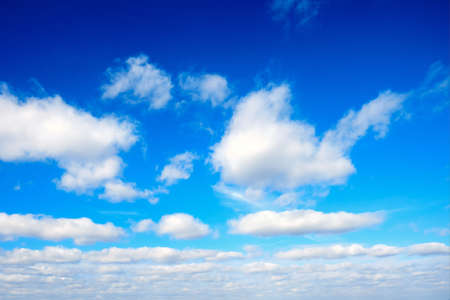 Spring azure sky with white fluffy clouds on a blue background