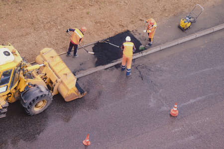 Workers fill a hole in the sidewalk laying new asphalt from the bucket of a bulldozer