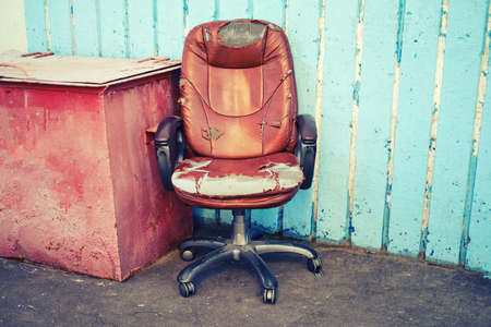 An old leather boss chair with ragged upholstery, bankruptcy concept and business problems. Blue wall with place for text, copy space Banque d'images