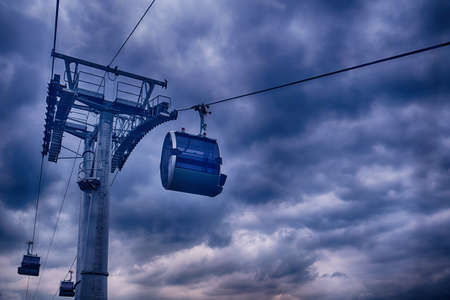 Cableway with cabs for transporting people against a stormy sky