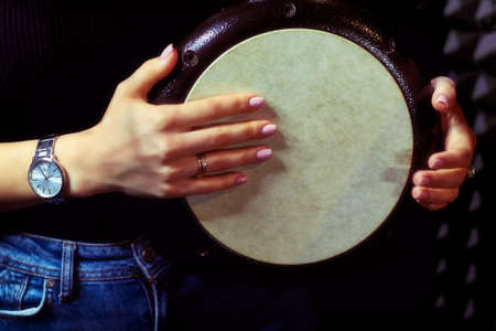 The girl plays the drum, which he holds in his hands. Metal darbuka, a kind of djembe on recording in the Studio. Fingers of a young woman on the leather membrane of the drum.