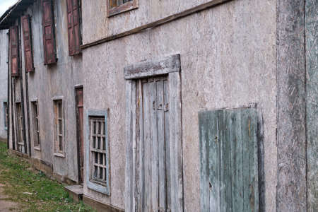 Walls of old houses with closed wooden shutters windows and boarded up doors