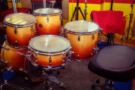 Orange drums and a black chair in the rehearsal room. Yellow and red walls in the room for musicians.