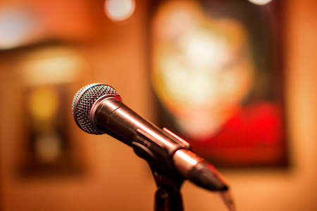 Microphone at a concert with a background in the form of pictures. Stage for performers with microphone stand for voice amplification and recording