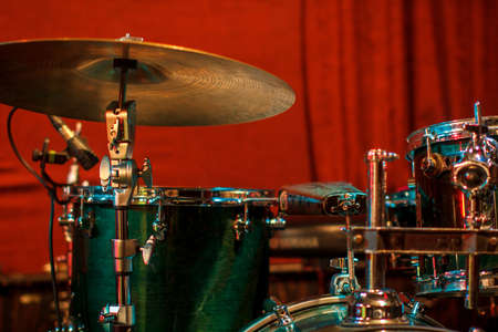 Green drum set on red background. Percussion instruments at a jazz concert. Drum and plates are on the stage of the concert hall