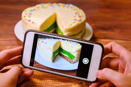 Women's hands with the phone taking pictures of the cake. Blogger shoots food . Create a photo for posting on the Internet. White phone and a tri-color cake on a wooden table. Archivio Fotografico