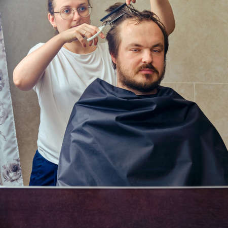 Wife cuts a man's hair with scissors in front of the mirror, copy space. The concept of unkempt appearance and problems in isolation from the coronavirus pandemic