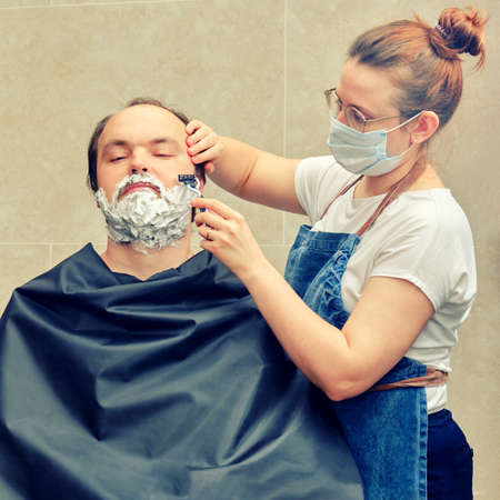 Woman barber in a medical mask shaves a man with a safety razor. Concept of unkempt appearance and problems in isolation from the coronavirus pandemic
