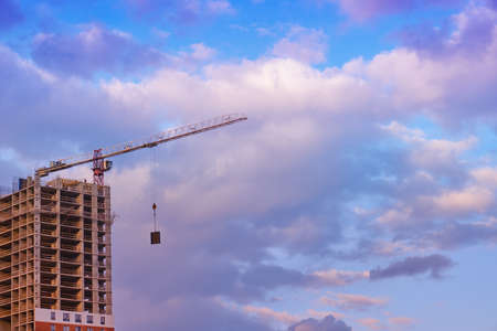 A tower crane lifts a load on a house under construction, copy space for inscription on a cloudy sky background Banco de Imagens