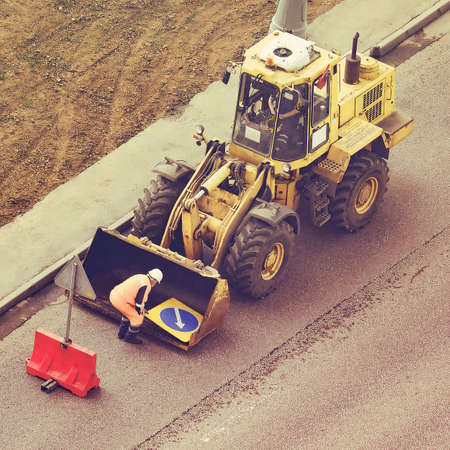 The worker finishes carrying out repair work on the road removing signs from the bucket of the excavator 写真素材