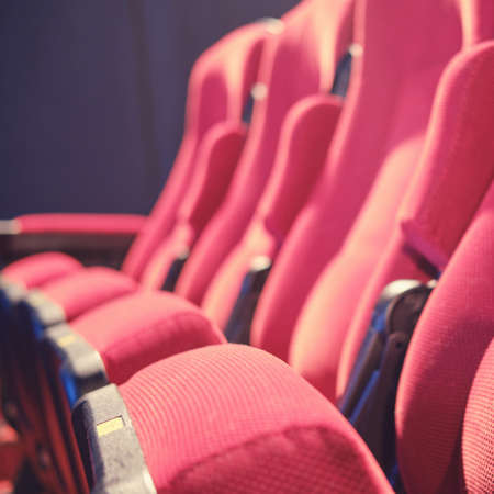 An empty row of chairs with no people in the auditorium. Problems during the coronavirus pandemic, concept with empty seats in cinema hall