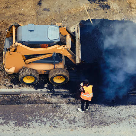 A road worker, a small bulldozer and a large pile of hot asphalt