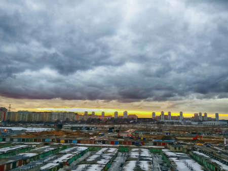 Dull suburban city landscape. Old garages and ruined industrial area of the city against the dramatic sky. An impending storm outside the city.