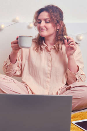 A woman looks at a laptop and drinks coffee with cookies. Girl has breakfast in the morning in the bedroom