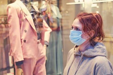 A young woman looks at a shop window during the coronavirus epidemic