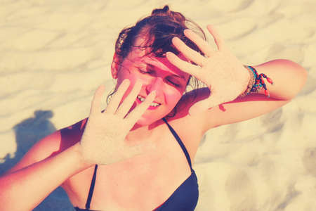 A woman with a burnt face protects her hands from the sun on the beach.