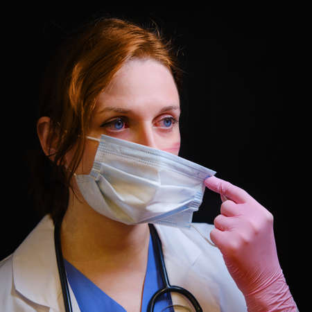 Nurse with red eyes removes the mask from his face after work and shows the wounds rubbed with protective clothing. Doctor after a shift in the hospital, close-up on a black background