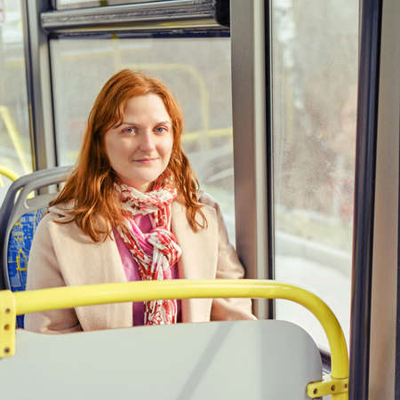 A redheaded woman smiles as she sits in a bus seat