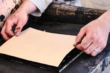 Hands men set the sheet on a retro printing press. Vintage typographic machine. 版權商用圖片