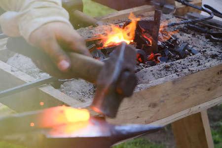 Blacksmith horn outdoors with burning coals, follow focus