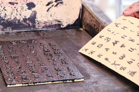 A man takes a printed sheet of paper. Cyrillic alphabet for printing in vintage style. Printing books old retro method. Standard-Bild