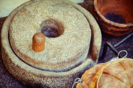 Hand millstones for making bread in ancient Rome. Reconstruction with the preparation of bread in the ancient Roman way. Retro lifestyle cooking.