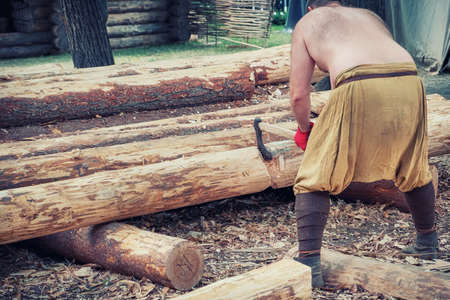 A lumberjack cuts a tree trunk lying on the ground. Man woodcutter in retro clothes with an ax.